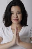 Pregnant woman standing in prayer posture - Asia Images Group