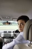 Man driving car, looking back over shoulder - Asia Images Group