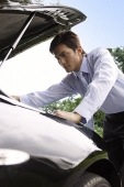 Businessman looking under hood of car - Asia Images Group