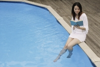 Young woman reading poolside - Asia Images Group