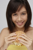 Young woman eating burger - Asia Images Group