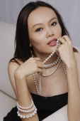 Young woman holding strand of pearls - Asia Images Group