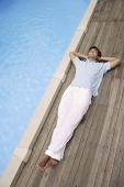 Man reclining by pool - Asia Images Group
