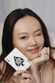 Young woman holding ace of spades card - Asia Images Group