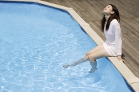 Young woman having fun by pool - Asia Images Group