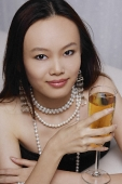 Young woman holding glass of champagne - Asia Images Group
