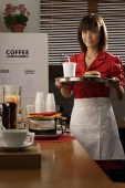Waitress in diner serving burger and drink - Asia Images Group
