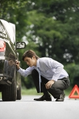 Man inspecting car - Asia Images Group
