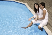 Young couple having fun by pool - Asia Images Group