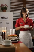 Waitress in diner holding coffee - Asia Images Group