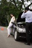 Man looking under hood of car while woman waits - Asia Images Group