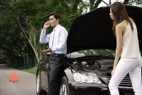 Woman looking under hood of car while man talks on phone - Asia Images Group