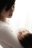 Woman holding sleeping baby - Asia Images Group