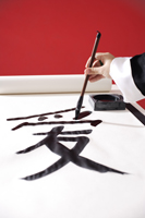 "Woman writing Chinese calligraphy ""Love"" - Asia Images Group"