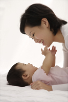 Woman playing with baby girl - Asia Images Group