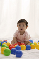 Baby girl playing with balls - Asia Images Group