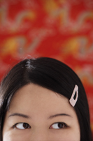 Cropped face of Chinese woman with pink hair clip - Asia Images Group