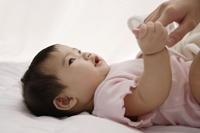 baby girl holding woman's hand - Asia Images Group