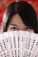 Chinese woman looking over hand-held fan with Chinese characters - Asia Images Group