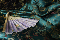 Detail of fan on top of jade green Chinese silk fabric - Asia Images Group