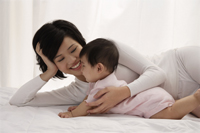 Woman lying on bed with baby girl - Asia Images Group