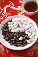 Still life of black and white melon seeds in shape of yin yang, cup of tea - Asia Images Group