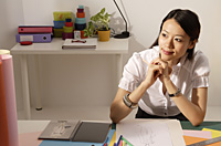 Chinese fashion designer smiling, thinking at work desk - Asia Images Group
