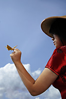 Chinese woman with conical hat holding a paper crane - Asia Images Group