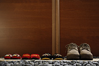 slippers and shoes placed in a row at door front - Asia Images Group