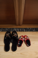 top view of red and black oriental slippers at door front - Asia Images Group