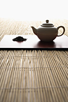 tea leaves in a pile and tea pot on bamboo mat - Asia Images Group