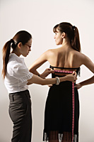 Chinese fashion designer measuring back of model's dress - Asia Images Group