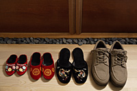 top view of slippers and shoes placed in a row at door front - Asia Images Group