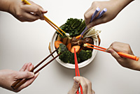 hands holding chopsticks in clay pot of vegetables - Asia Images Group