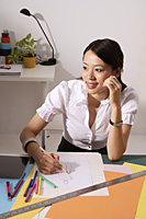 Chinese fashion designer smiling, sketching at work desk - Asia Images Group