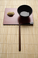 steam gyoza dumpling with sauce in bowl and chopstick on bamboo mat - Asia Images Group
