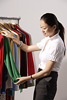 Chinese fashion designer selecting clothes from rack - Asia Images Group
