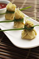 3 wanton dumplings placed in a row on a white plate with chili sauce on the side - Asia Images Group
