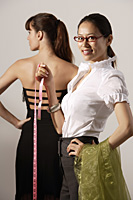 Chinese fashion designer measuring model's dress, smiling at camera - Asia Images Group