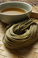 cooked soba noodles with sauce on the side placed on bamboo tray closeup - Asia Images Group