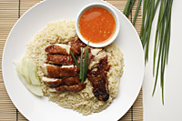 chicken rice with chili sauce on the side on white plate - Asia Images Group