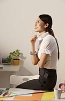 Chinese fashion designer sitting on work desk, thinking - Asia Images Group