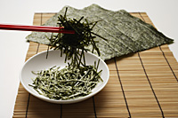 seaweed shreds picked up by red chopstick with seaweed sheets in background - Asia Images Group