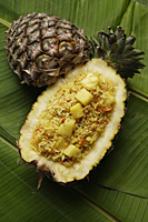 pineapple rice in fruit shell on banana leaf - Asia Images Group