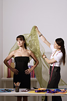 Chinese fashion designer draping cloth over model, taking measurements - Asia Images Group