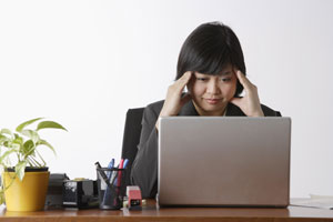 business woman looking stressed at computer - Asia Images Group