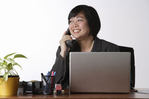 woman sitting at desk talking on phone - Asia Images Group