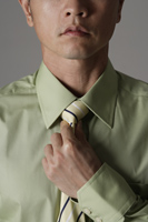 crop portrait of man tightening tie - Asia Images Group