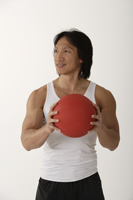 Chinese man holding medicine ball - Asia Images Group