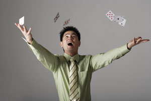 man throwing cards up into the air - Asia Images Group
